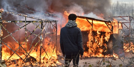 A migrant looks at shacks burning during the dismantling of half of the