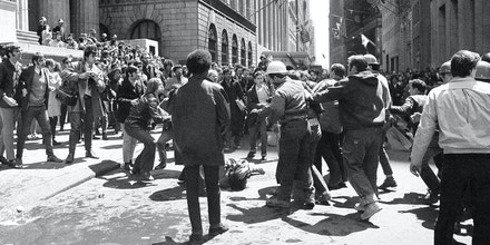 Construction workers and young anti-war protesters scuffle near Broad and Wall Streets in New York, May 7, 1970. One victim of the straggle, lying in center near manhole, covers his head as students at left and workers exchange jeers. Fight broke out when about 20 construction workers holding American flags marched trough the intersection jammed with 1,000 youths. Police restored order after a few minutes. (AP Photo/John Rooney)