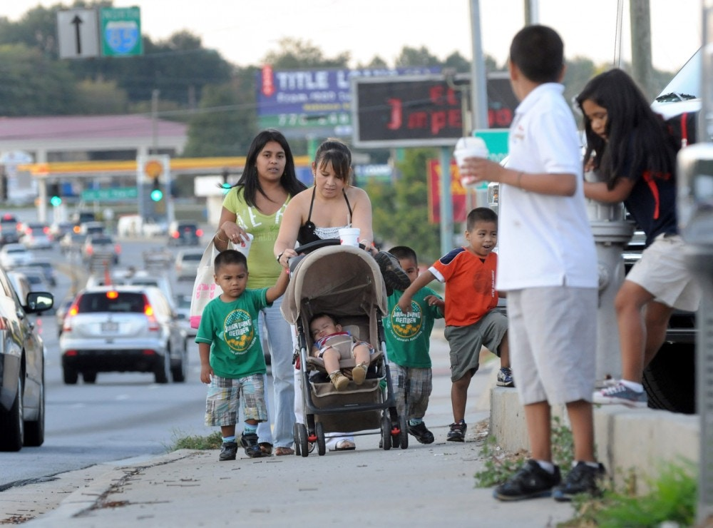 In this photo taken Thursday Sept. 30, 2011, undocumented immigrants from Mexico, Rocio Martinez, left, and Aura Consuelo Morales walk with their children along Jimmy Carter Blvd. in Norcross, Ga. The two women walk great distances everyday as they would risk deportation if they drove a car without a driver's license because the enforcement of the 287(g) program in their community which allows state and local law enforcement agencies to question anyone on their immigration status for any infraction of the law such as driving without a license. In a state where a majority of the population gets around by car, many of the undocumented families can be seen walking along the busy avenues to the grocery store, the doctor or the parks. (AP Photo/Erik S. Lesser)