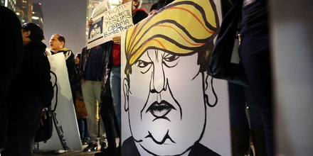 NEW YORK, NY - DECEMBER 10: A protester holds a caricature of conservative presidential candidate Donald Trump during a demonstration against racism and Trump's recent remarks concerning Muslims on December 10, 2015 in New York City. Dozens or demonstrators and activists converged at Columbus Circle to denounce the politics of Trump and the treatment of Muslim refugees both in America and Europe.  (Photo by Spencer Platt/Getty Images)