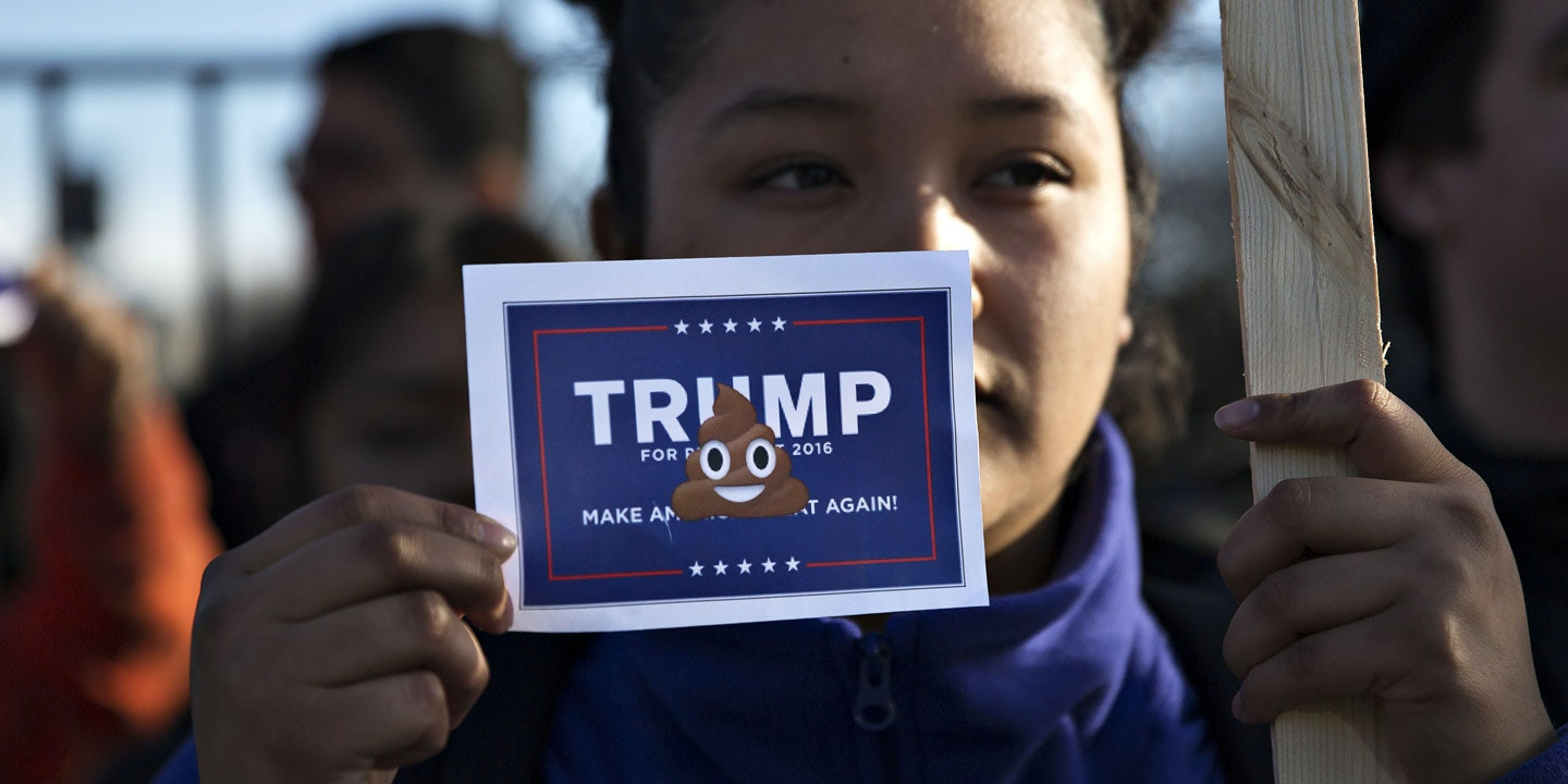 A demonstrator holds a sign outside a campaign event for Donald Trump, president and chief executive of Trump Organization Inc. and 2016 Republican presidential candidate, not pictured, in Chicago, Illinois, U.S., on Friday, March 11, 2016. Trump's raucous campaign tour makes its first stops today in U.S. cities still wrestling with racial tension spawned by police shootings, just as his rallies have turned increasingly violent. Photographer: Daniel Acker/Bloomberg via Getty Images