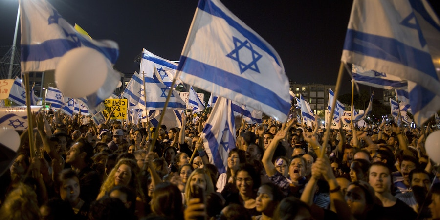 TEL AVIV, ISRAEL - APRIL 19:  Israelis hold up flags during a rally in support of Israeli soldier Elor Azaria on April 19, 2016 in Tel Aviv, Israel. Sergeant Azaria, 20, was charged on Monday with manslaughter for killing Abed al Fatah a-Sharif, who was lying on the ground seriously wounded after he and another Palestinian attacked IDF soldiers in Hebron.   (Photo by Lior Mizrahi/Getty Images)