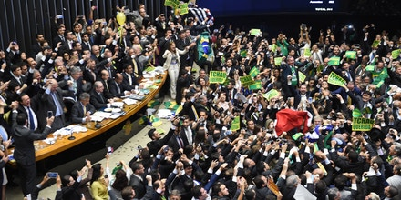 TOPSHOT - Brazil's lawmakers celebrate after they reached the votes needed to authorize President Dilma Rousseff's impeachment to go ahead, at the Congress in Brasilia on April 17, 2016.Brazilian lawmakers on Sunday reached the two thirds majority necessary to authorize impeachment proceedings against President Dilma Rousseff. The lower house vote sends Rousseff's case to the Senate, which can vote to open a trial. A two thirds majority in the upper house would eject her from office. Rousseff, whose approval rating has plunged to a dismal 10 percent, faces charges of embellishing public accounts to mask the budget deficit during her 2014 reelection. / AFP / EVARISTO SA (Photo credit should read EVARISTO SA/AFP/Getty Images)
