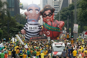 "Demonstrators parade large inflatable dolls depicting Brazil's former President Luiz Inacio Lula da Silva in prison garb and current President Dilma Rousseff dressed as a thief, with a presidential sash that reads ""Impeachment,"" in Sao Paulo, Brazil, Sunday, March 13, 2016. The corruption scandal at the state-run oil giant Petrobras has ensnared key figures from Rousseff's Workers' Party, including her predecessor and mentor, Lula da Silva, as well as members of opposition parties. (AP Photo/Andre Penner)"