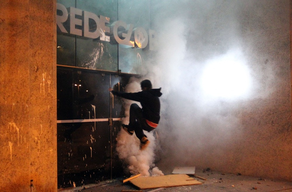 Protesters destroy a building entrance channel TV, Rede Globo, in Leblon, Rio de Janeiro, southeastern Brazil, this morning, July 18, 2013. The protest was against the governor of Rio de Janeiro, Sérgio Cabral. Photo: MARCOS DE PAULA/ESTADAO CONTEUDO. (Agencia Estado via AP Images)