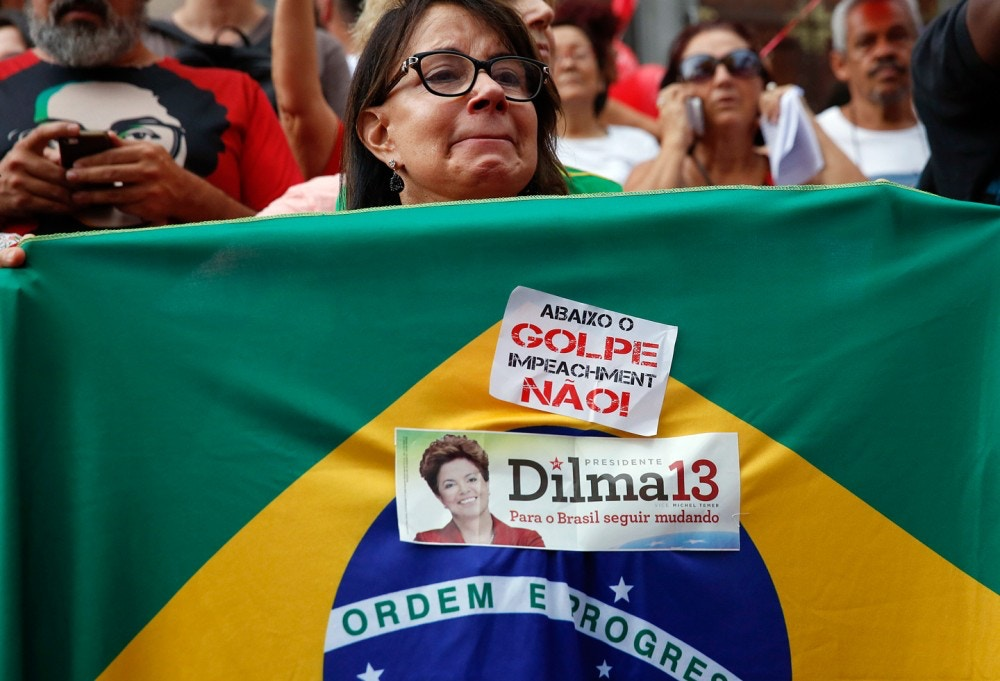 "A demonstrator holds a Brazilian flag with a sticker that reads in Portuguese ""Down with the coup, impeachment no"" during a protest in support of Brazil's President Dilma Rousseff and former President Luiz Inacio Lula da Silva in Sao Paulo, Brazil, Thursday, March 31, 2016. Rousseff is currently facing impeachment proceedings as her government faces a stalling national economy and multiple corruption scandals. Lula da Silva has been linked to a sprawling corruption scandal involving Brazilian oil giant Petrobras. (AP Photo/Andre Penner)"