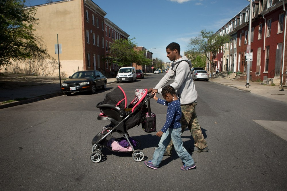 Shaun Young walks with his daughters Jordyn, 5, and Korie, 4 months, in their neighborhood, a few blocks from where Freddie Gray, who died while in police custody just over one year ago, was arrested in Baltimore, Maryland, April 23, 2016. (photo by Allison Shelley)