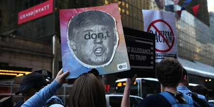 NEW YORK, USA - APRIL 14: Protesters gather outside of the Grand Hyatt Hotel during a demonstration against US Republican presidential candidate Donald Trump and his racist, Islamophobic hate speech in New York, NY, United States on April 14, 2016. US Republican presidential candidate Donald Trump wants 'total and complete shutdown of Muslims entering the United States' as well as he said 'All Muslim immigration to the United States should be halted'. (Photo by Cem Ozdel/Anadolu Agency/Getty Images)