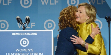 Former US Secretary of State Hillary Rodham Clinton (R) hugs DNC Chair Rep. Debbie Wasserman Schultz (L), D-FL, as Clinton arrives on stage to speak at the Democratic National Committee's Womens Leadership Forum Issues Conference in Washington, DC on September 19, 2014. AFP PHOTO/Mandel NGAN        (Photo credit should read MANDEL NGAN/AFP/Getty Images)
