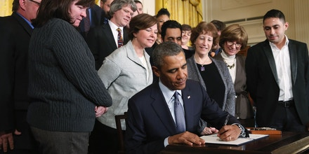 WASHINGTON, DC - MARCH 13:  U.S. President Barack Obama signs a presidential memorandum for overtime protections for workers during an event in the East Room at the White House, on March 13, 2014 in Washington, DC.  The memorandum will direct the Department of Labor construct a new set of overtime rules to make ore emplyees eligible to overtime pay.  (Photo by Mark Wilson/Getty Images)