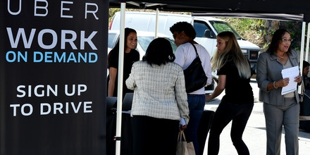 People sign up to become Uber drivers at the first of Uber's 'Work On Demand' recruitment events where they hope to sign 12,000 new driver-partners, in South Los Angeles on March 10, 2016. / AFP / Mark Ralston        (Photo credit should read MARK RALSTON/AFP/Getty Images)