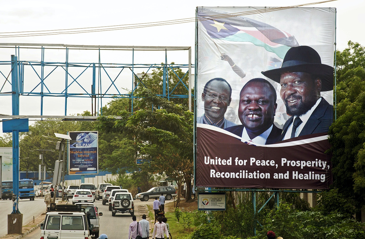 Pedestrians and traffic move past a billboard featuring portraits of the South Sudan's President Salva Kiir (R) and the opposition leader Riek Machar (C) in Juba, South Sudan, on April 14, 2016.<br /> Preparations are on to forge a unity government with Machar taking the post of vice president. Machar's return to the capital Juba is expected on April 18, 2016. It is potentially one of the most significant steps towards peace since a repeatedly broken deal made in August 2015. The two leaders come from the south's two main ethnic groups, Kiir from the Dinka people and Machar from the Nuer. They fought both alongside and against each other during the long and bitter war with Khartoum. Civil war erupted in December 2013 after Kiir accused troops loyal to Machar of staging a failed coup, a claim Machar denies. The pair are now due to set up a transitional unity government.   / AFP / cds / ALBERT GONZALEZ FARRAN        (Photo credit should read ALBERT GONZALEZ FARRAN/AFP/Getty Images)