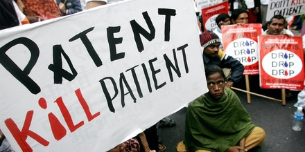 New Delhi, INDIA: Indian people infected with HIV and activists hold placards and shout slogans against Swiss pharmaceutical firm Novartis during a demonstration in New Delhi, 29 January 2007, urging the company to withdraw a case against the Indian government's laws on drug patents. Novartis aims at challenging the patent laws in India, which will make several life saving drugs like anti-HIV ,cancer medicines severely expensive and beyond the means of common people in scores of developing countries that source cheap drugs from India.  AFP PHOTO/ Manan VATSYAYANA (Photo credit should read MANAN VATSYAYANA/AFP/Getty Images)