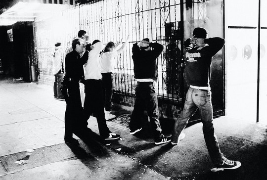 A Los Angeles police officer searches members of the 18th Street gang during a 1987 sweep in the downtown on Aug. 11, 1987 in Los Angeles.(AP Photo)