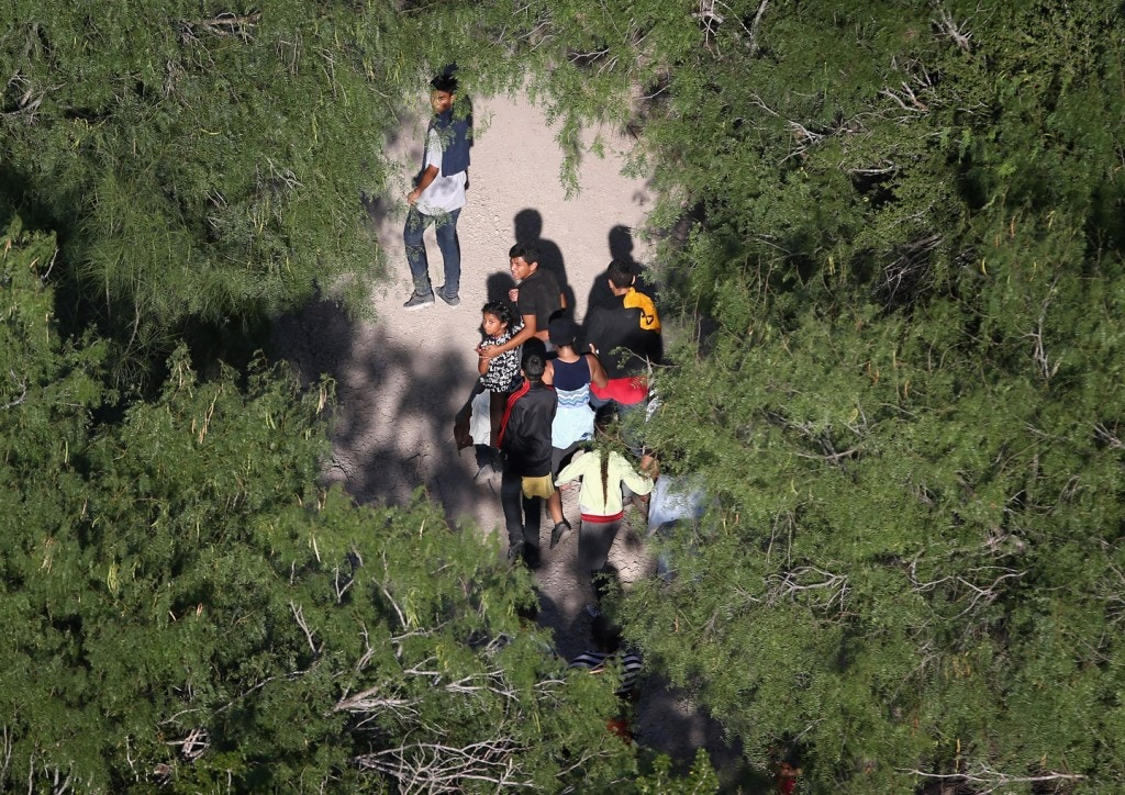 MCALLEN, TX - JULY 21:  Undocumented immigrant families walk before being taken into custody by Border Patrol agents on July 21, 2014 near McAllen, Texas. Thousands of immigrants, many of them minors from Central America, have crossed illegally into the United States this year, causing an unprecentented humanitarian crisis on the U.S.-Mexico border. Texas Governor Rick Perry announced that he will send 1,000 National Guard troops to help stem the flow. (Photo by John Moore/Getty Images)
