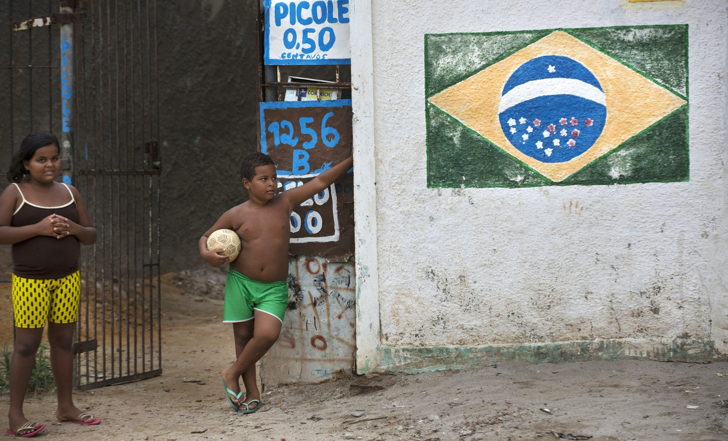 Children stand outside a small store in Olinda, Brazil, on Wednesday, Jan. 20, 2016.
