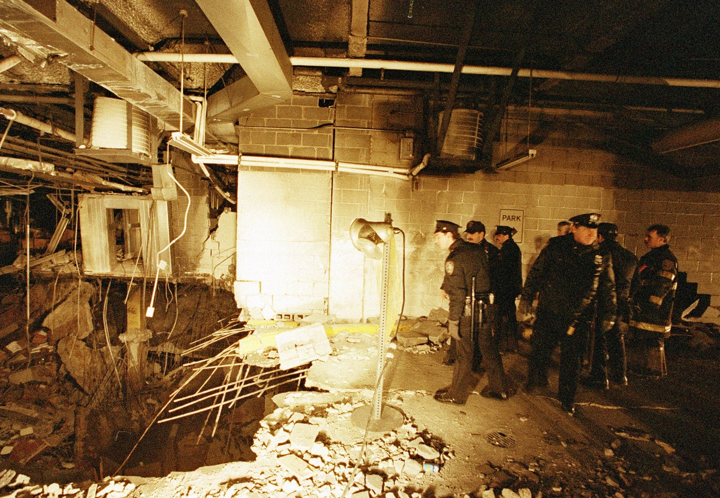 Police and firefighters inspect the bomb crator inside an underground parking garage of New York's World Trade Center the day after an explosion tore through it, Feb. 27, 1993.