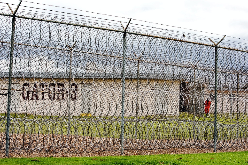 "FILE - This April 22, 2009, file photo, shows a prisoner, far right, seen behind layers of wire razor fencing at the Louisiana State Penitentiary at Angola, La. Albert Woodfox, the last of three high-profile Louisiana prisoners known as the ""Angola Three,"" could walk free within days after a federal judge ordered state officials to release him immediately. Woodfox has been in solitary confinement for 43 years. He was accused, along with three other prisoners, in the stabbing death of Brent Miller, a 23-year-old guard at the Louisiana State Penitentiary at Angola. (AP Photo/Judi Bottoni, File)"