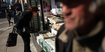 NEW YORK, NY - APRIL 03:  Jerry Delakas, 63, (R) a longtime newspaper vendor in Manhattan's Cooper Square, stands by his newsstand on April 3, 2012 in New York City. Delakas has been selling papers, magazines, lottery tickets and other items seven days a week for 25 years at the iconic New York location. Despite the license holder for the newsstand leaving it to him in her will, Delakas is being threatened with eviction by the Department of Consumer Affairs. The New york agency claims that he's not the legal license holder. The area around Astor Place at Lafayette Street, once the heart of bohemian New York, has slowly evolved into an area of banks and chain stores like Starbucks and The Gap. Critics of the city's threat to evict Delakas say that he represents some of the last traces of authentic New York.  (Photo by Spencer Platt/Getty Images)