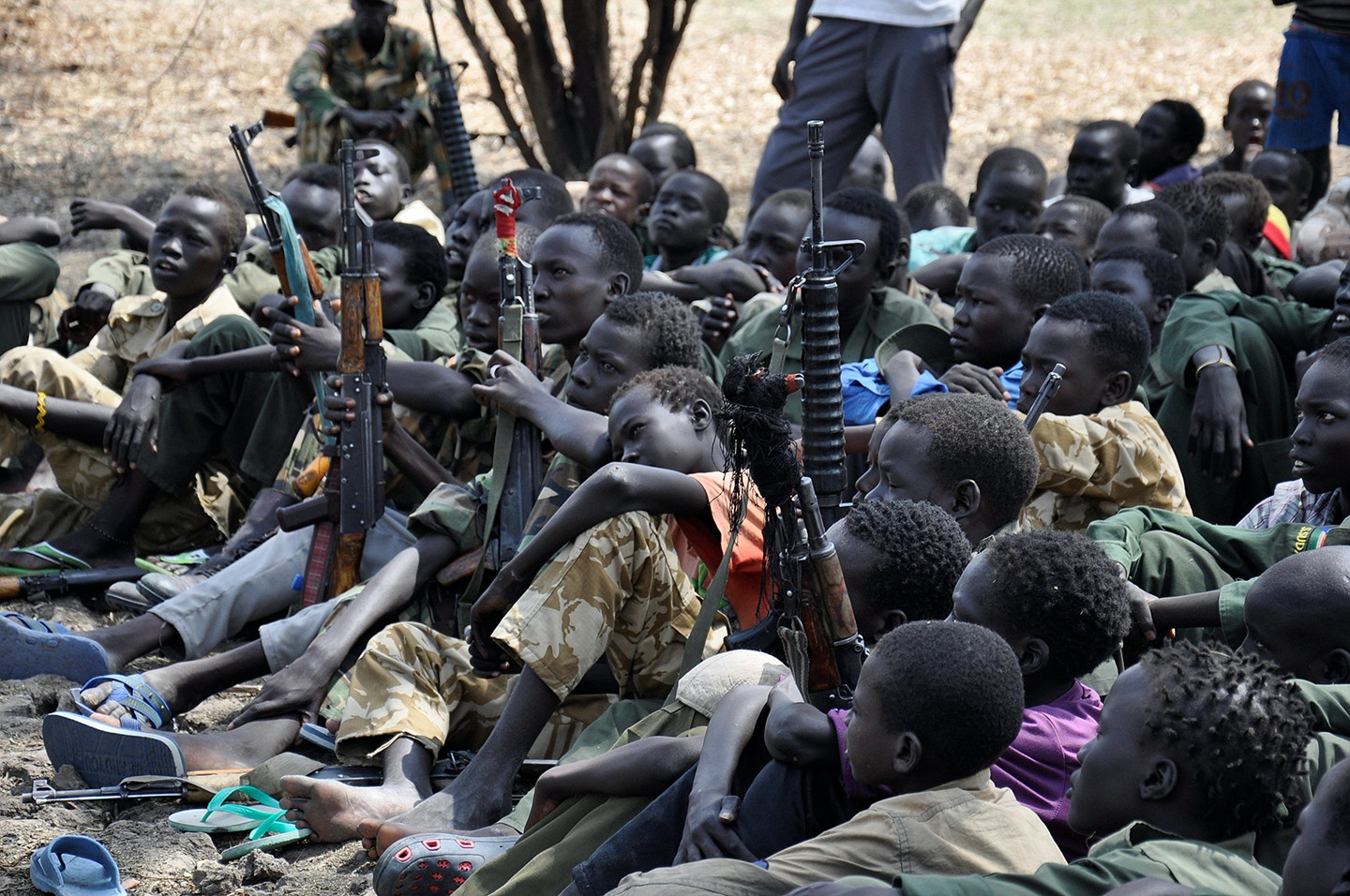 PIBOR, SOUTH SUDAN - FEBRUARY 10 : Young boys, children soldiers sit on February 10, 2015 with their rifles at a ceremony of the child soldiers disarmament, demobilization and reintegration in Pibor over sawn by UNICEF and partners. The children in Pibor, Jonglei State, surrendered their weapons and uniforms in a ceremony overseen by the South Sudan National Disarmament, Demobilization and Reintegration Commission, and the Cobra Faction and supported by UNICEF. (Photo by Samir Bol /Anadolu Agency/Getty Images)