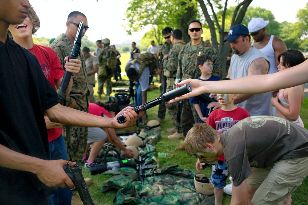 Marines land attack helicopters, paint children in camouflage and unfurl infantry weapons, including pistols with silencers for the public's amusement with the unspoken aim of recruiting new marines. Some of the young men had just signed up to go to Iraq, Orchard Beach, the Bronx, New York,  2007