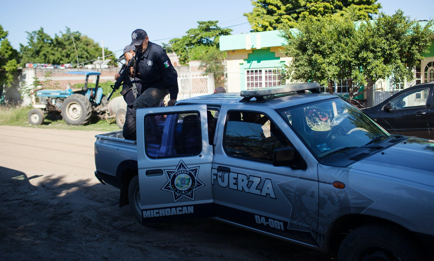 Members of the Fuerza Rural, more specifically a group lead by Hipolito Mora, get out of a truck in front of Mora's house, in La Ruana, Michoacán, Mexico, Tuesday, December 15, 2015. Hipolito Mora was one of the original founder of the autodefensa movement, which saw vigilantes spread across the state of Michoacán and drive out the cartel group the 'Knights of Templar'. Since the uprising began in 2013, other criminal groups have filled the space of the previous cartel and many look at the autodefensa movement as a failure. Mora has had many challenges over the last three years, including being sent to jail twice and having his son killed in a shootout Dec. 16, 2014 during a shootout with a rival group.<br /> (Brett Gundlock/Boreal Collective)