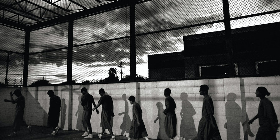 Inmates, ages 10-16, march at dawn through the exercise yard at the Webb County Juvenile Detention facility.