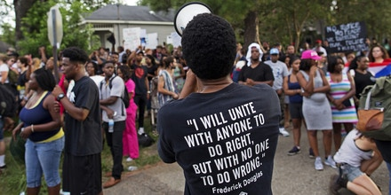 Protesters demonstrate a residential neighborhood in Baton Rouge, La. on Sunday, July 10, 2016. After an organized protest in downtown Baton Rouge protesters wandered into residential neighborhoods and toward a major highway that caused the police to respond by arresting protesters that refused to disperse. (AP Photo/Max Becherer)