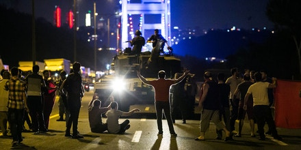 EDITORS NOTE: Graphic content / People take over a tank near the Fatih Sultan Mehmet bridge during clashes with military forces in Istanbul on July 16, 2016. Istanbul's bridges across the Bosphorus, the strait separating the European and Asian sides of the city, have been closed to traffic. Turkish military forces on July 16 opened fire on crowds gathered in Istanbul following a coup attempt, causing casualties, an AFP photographer said. The soldiers opened fire on grounds around the first bridge across the Bosphorus dividing Europe and Asia, said the photographer, who saw wounded people being taken to ambulances. / AFP / GURCAN OZTURK (Photo credit should read GURCAN OZTURK/AFP/Getty Images)
