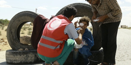 A young girl receives first aid for a shrapnel wound at a road block set up by fighters from the Syrian Democratic Forces (SDF) on June 10, 2016 on the outskirts of the northern Syrian town of Manbij, held by the Islamic State (IS) group, as they encircled the town cutting off the jihadists main supply route between Syria and Turkey.IS lost control of a vital supply artery when the troops completely surrounded the town of Manbij, at the heart of the last stretch of territory along Turkey's border still under the jihadists' control. / AFP / DELIL SOULEIMAN (Photo credit should read DELIL SOULEIMAN/AFP/Getty Images)