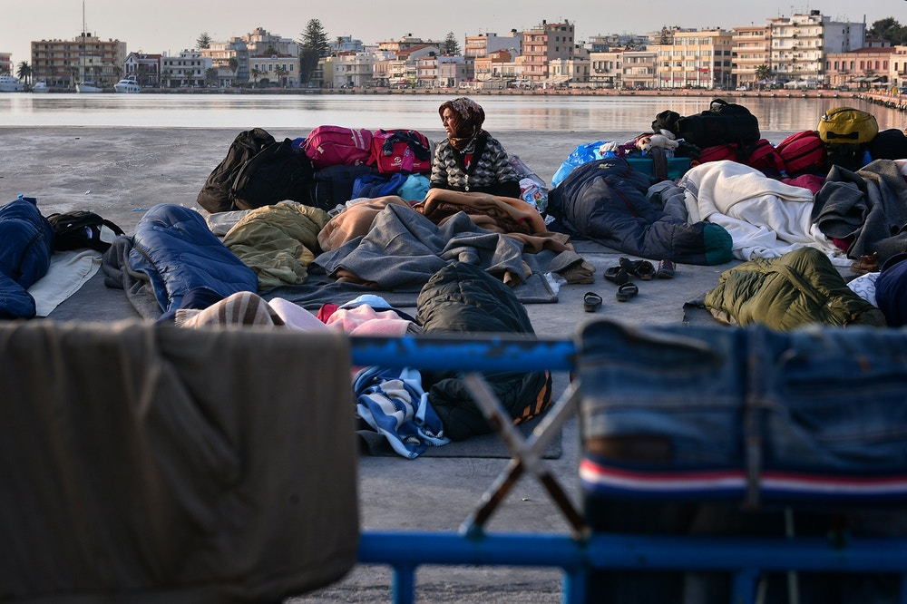 "A woman wakes up in the port of Chios, where refugees and migrants who managed to leave the VIAL detention center a few days ago are camping out on April 5, 2016.<br /><br /><br /><br /><br /><br /><br /><br /><br /><br /><br /><br /><br /><br /><br /><br /> Greece sent a first wave of migrants back to Turkey on April 4 under an EU deal that has faced heavy criticism from rights groups. Under the agreement, designed to halt the main influx which comes from Turkey, all ""irregular migrants"" arriving since March 20 face being sent back, although the deal calls for each case to be examined individually. For every Syrian refugee returned, another Syrian refugee will be resettled from Turkey to the EU, with numbers capped at 72,000.  / AFP / LOUISA GOULIAMAKI        (Photo credit should read LOUISA GOULIAMAKI/AFP/Getty Images)"