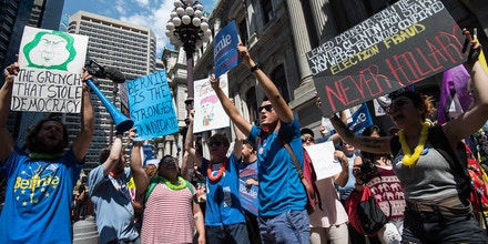 Supporters of former US Democratic presidential candidate Bernie Sanders hold signs at a rally at City Hall in Philadelphia on July 25, 2016, as Democrats gather to formally annoint Hillary Clinton as their candidate for the November presidential election at the Democratic National Convention. / AFP / NICHOLAS KAMM        (Photo credit should read NICHOLAS KAMM/AFP/Getty Images)