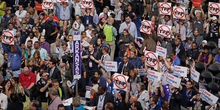 Delegates hold up anti-TPP signs on the floor during Day 1 of the Democratic National Convention at the Wells Fargo Center in Philadelphia, Pennsylvania, July 25, 2016.  / AFP / Brendan Smialowski        (Photo credit should read BRENDAN SMIALOWSKI/AFP/Getty Images)