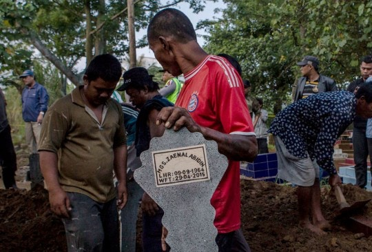 CILACAP, CENTRAL JAVA, INDONESIA - APRIL 29:  A worker holds a tombstone of Zaenal Abidin, one of the eight drug convicts, during a funeral service after the execution at Nusakambangan prison on April 29, 2015 in Cilacap, Central Java, Indonesia. Chan and Sukumaran were both sentenced to death after being found guilty of attempting to smuggle 8.3kg of heroin valued at around $4 million from Indonesia to Australia along with 7 other accomplices.  (Photo by Ulet Ifansasti/Getty Images)
