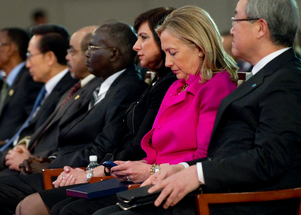 U.S. Secretary of State Hillary Clinton (2nd R) checks her phone while sitting next to South Korean Foreign Minister Kim Sung-hwan (R) at the Fourth High Level Forum on Aid Effectiveness in Busan November 30, 2011.  REUTERS/Saul Loeb/Pool  (SOUTH KOREA - Tags: POLITICS) (Newscom TagID: rtrlfour932049.jpg) [Photo via Newscom]
