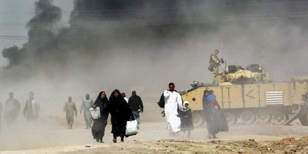 FILE -- In this March 29, 2003 file photo, Iraqis pass by a British tank as they flee Basra, southern Iraq, as smoke looming over the city can be seen in the distance. The head of Britain's Iraq War inquiry, retired civil servant John Chilcot, released a damning report Wednesday, July 6, 2016, on a conflict he said was mounted on flawed intelligence and executed with