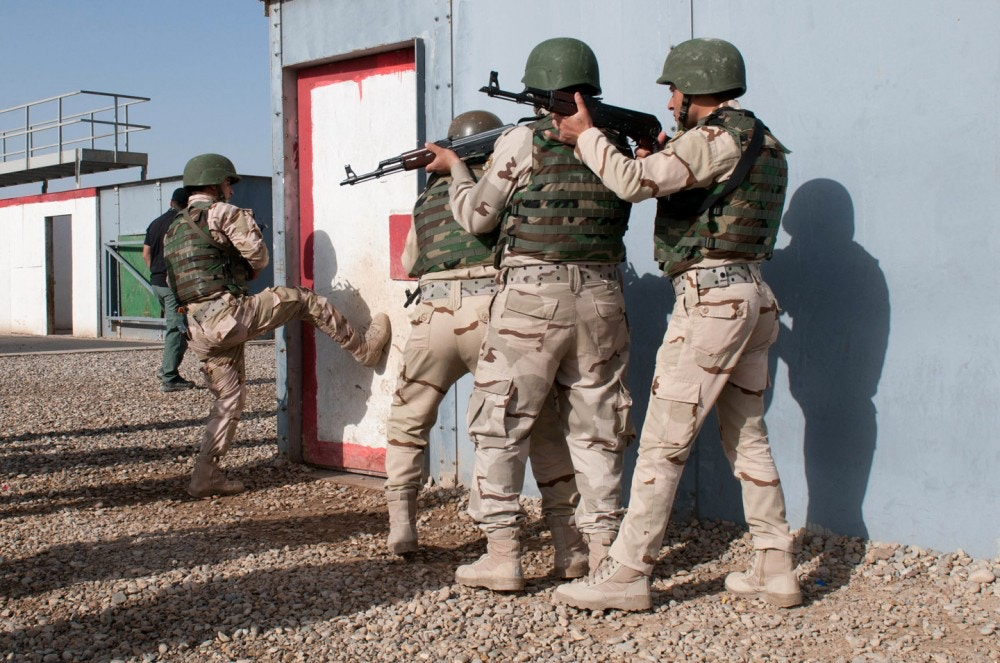 A soldier of the Iraqi army's 16th Division kicks in a door of a building during a training exercise at Besmaya Range Complex, Iraq March 21, 2015. U.S. Soldiers with  2nd Battalion, 505th Parachute Infantry Regiment, 3rd Brigade Combat Team, 82nd Airborne Division and the Spanish Army's Spanish Legion are advising the training to  strengthen the Iraqi army's ability to fight enemy forces in their country. (Sgt. Deja Borden, CJTF-OIR)
