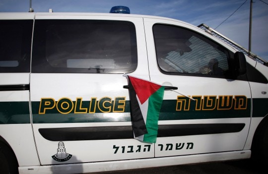 "A Palestinian national flag is hung on an Israeli police car by Israeli and Palestinian peace activist during a demonstration organised by the ""Combatants for Peace"" association at an Israeli road  near a checkpoint between the West Bank city of Beit Jala and Jerusalem, on November 27, 2015. Hundreds of protesters gathered to denounce the occupation and all violence in the region. AFP PHOTO / THOMAS COEX / AFP / THOMAS COEX        (Photo credit should read THOMAS COEX/AFP/Getty Images)"