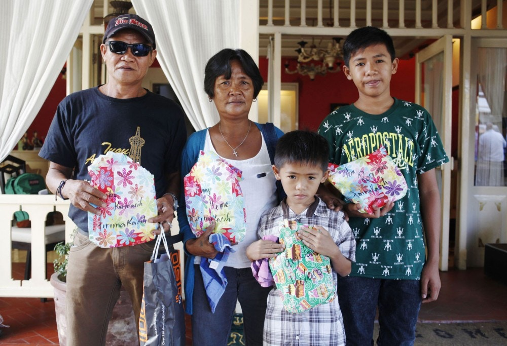 Family members of Philippine death row drug convict Mary Jane Veloso, (L-R) father Caesar Veloso, mother Celia Veloso and sons Mark Darren and Mark Danniel show the press presents they brought as they wait outside the Yogyakarta prison, in Yogyakarta on January 12, 2016, before visiting Mary to celebrate her 31st birthday. Veloso was sentenced to death in Indonesia after being arrested in 2009 with 2.6 kilograms (5.7 pounds) of heroin sewn into the lining of her suitcase. She had been due to face the firing squad along with other foreign drug convicts in April but was granted a temporary reprieve after a woman suspected of recruiting her was arrested in the Philippines. AFP PHOTO / Suryo WIBOWO / AFP / SURYO WIBOWO        (Photo credit should read SURYO WIBOWO/AFP/Getty Images)