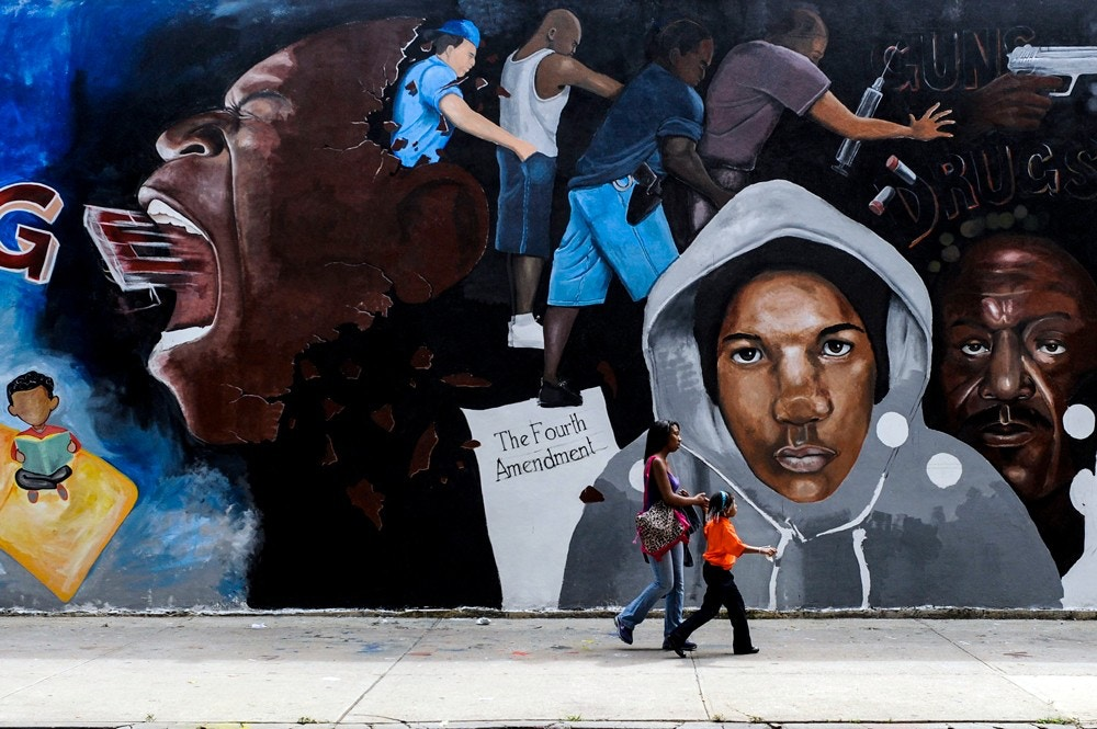 A street mural depicts police officers using the stop-and-frisk tactic in New York, Aug. 20, 2012.