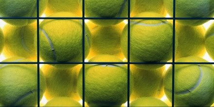 Tennis balls in metal basket, close-up