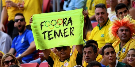 A man holds a sign against Brazil's acting President Michel Temer during the Rio 2016 Olympic Games First Round Group A men's football match Brazil vs South Africa, at the Mane Garrincha Stadium in Brasilia on August 4, 2016. / AFP / EVARISTO SA        (Photo credit should read EVARISTO SA/AFP/Getty Images)