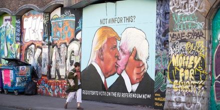 BRISTOL, UNITED KINGDOM - MAY 24:  A woman passes a mural that has been painted on a derelict building in Stokes Croft showing US presidential hopeful Donald Trump sharing a kiss with former London Mayor Boris Johnson on May 24, 2016 in Bristol, England. Boris Johnson is currently one of the biggest names leading the campaign for Britain to leave the European Union in the referendum which takes place on June 23 and Republican presidential hopeful Donald Trump has also backed a so-called Brexit.  (Photo by Matt Cardy/Getty Images)