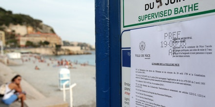 This picture taken on August 19, 2016 shows the bylaw forbidding women to wear Burkini at the beach in Nice, southeastern France on August 19, 2016. Nice has become the latest French seaside resort to ban the burkini, the body-concealing Islamic swimsuit that has sparked heated debate in secular France. Using language similar to bans imposed in a string of other towns on the French Riviera, the city barred apparel that