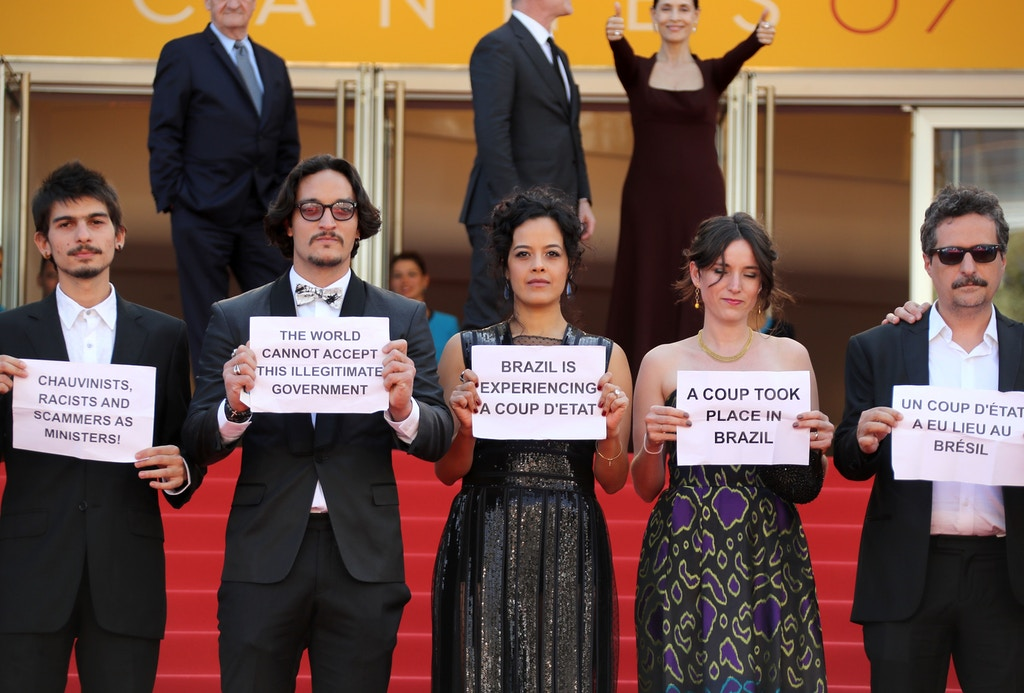 "(FromL) Brazilian actor Pedro Queiroz, Brazilian actor Allan Souza, Brazilian actress Maeve Jinkings, French-Brazilian producer Emilie Lesclaux and Brazilian director Kleber Mendonca Filho hold protest signs as they arrive on May 17, 2016 for the screening of the film ""Aquarius"" at the 69th Cannes Film Festival in Cannes, southern France.  / AFP / Valery HACHE        (Photo credit should read VALERY HACHE/AFP/Getty Images)"