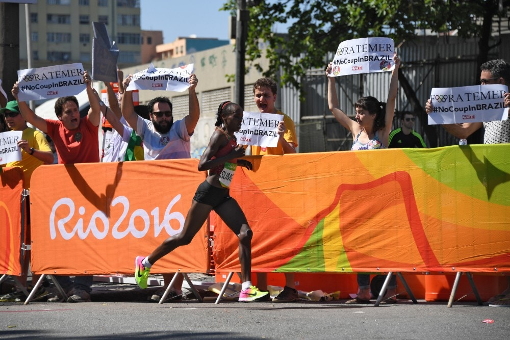 "RIO DE JANEIRO, BRAZIL - AUGUST 14:  Kenya's Jemima Jelagat Sumgong runs past protester holding banner against Brazil's interim leader reading ""Fora Temer"" (Temer out) in the finish area of the Women's Marathon during the athletics event at the Rio 2016 Olympic Games at Sambodromo in Rio de Janeiro on August 14, 2016.    (Photo by Johannes EISELE-Pool/Getty Images)"