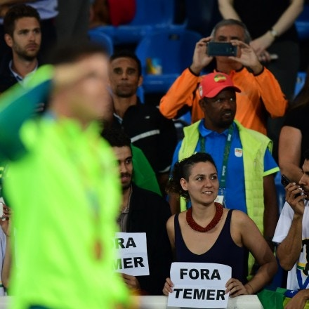 "Gold medallist Brazil's Thiago Braz Da Silva (L) celebrates on the podium as people hold a banner reading ""out with Temer"" (Brazil's interim president Michel Temer) at the medal ceremony for the men's pole vault during the athletics event at the Rio 2016 Olympic Games at the Olympic Stadium in Rio de Janeiro on August 16, 2016. / AFP / FRANCK FIFE        (Photo credit should read FRANCK FIFE/AFP/Getty Images)"