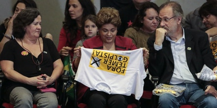 Brazilian suspended President Dilma Rousseff (C) holds a T-shirt reading