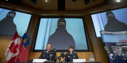 Video footage showing Aaron Driver is seen behind Royal Canadian Mounted Police (RCMP) Deputy Commissioner Mike Cabana, left, and Assistant Commissioner Jennifer Strachan during a press conference for what the RCMP are calling a terrorism incident Wednesday, in Strathroy, Ontario, on Thursday, Aug. 11, 2016 in Ottawa. Driver, a Canadian man previously banned from associating with Islamic State extremists, prepared a martyrdom video and was about to commit a terrorist attack but was killed when he prematurely detonated his explosive device in a taxi and was shot at by officers who say they thwarted the suicide bomb plot after being tipped off by the FBI, police said Thursday.  (Justin Tang/The Canadian Press via AP)