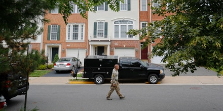 A law enforcement officer walks on the street outside the home of Nicholas Young, a Washington Metro Transit Officer, Wednesday, Aug. 3, 2016, in Fairfax, Va., Young was arrested at Metro's headquarters in Washington and charged with a single count of attempting to provided material support to a terrorist group. (AP Photo/Pablo Martinez Monsivais)